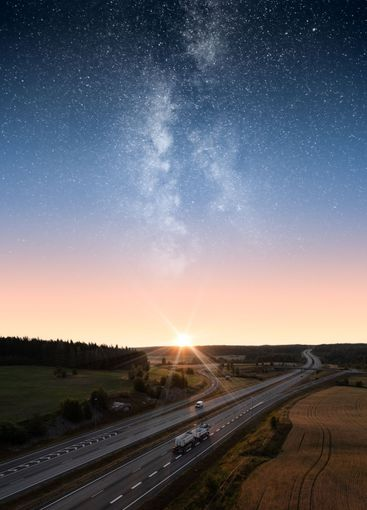 Vehicles on a freeway under an epic star sky and milky way