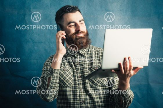 Young hipster man with beard concept working with a...