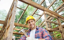Smiling Construction Worker Hammering In Timber Cabin