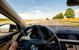 Man hand holding steering wheel driving with 135 KMh