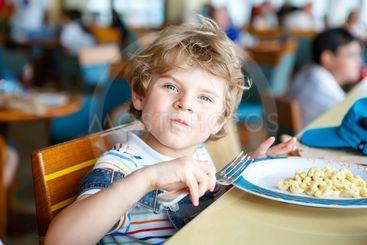 Cute healthy preschool boy eats pasta sitting in school...