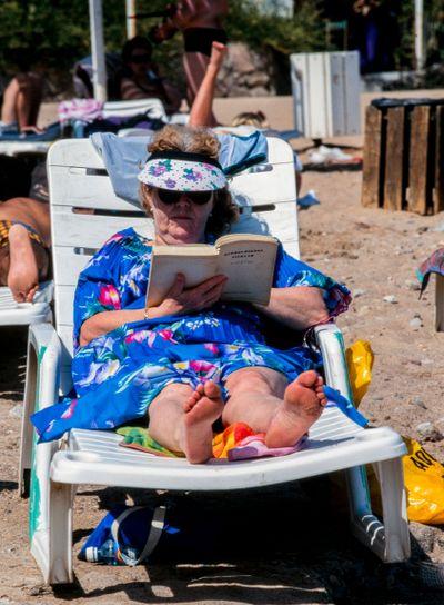 En dam ligger i en solstol på stranden och läser