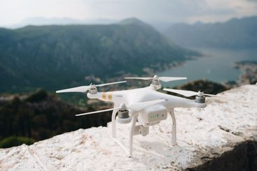 A white drone builds on a rock, ready to take off.