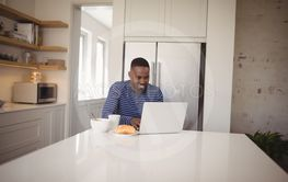 Smiling man using laptop while having breakfast in kitchen