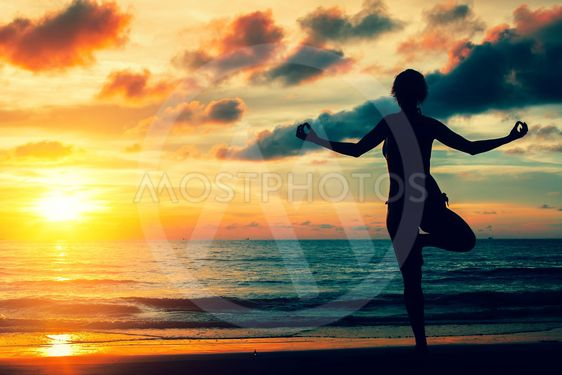Woman practicing yoga on the ocean coast during a magical...