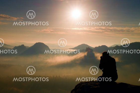 Photograph takes photos of daybreak above  heavy misty...