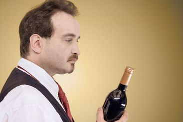 Man looking at wine bottle