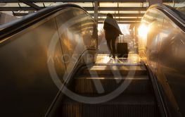 Escalators stairs and young woman traveler silhouette