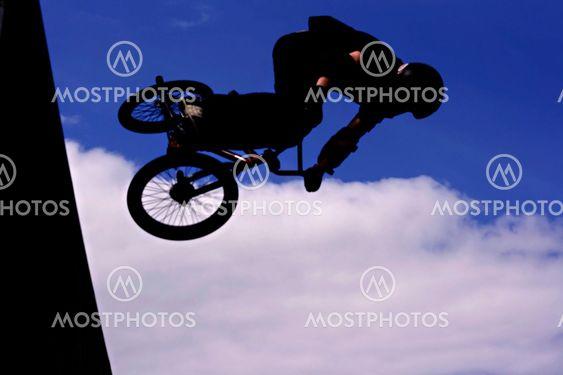 Silhouetted biker dreng gør stunts