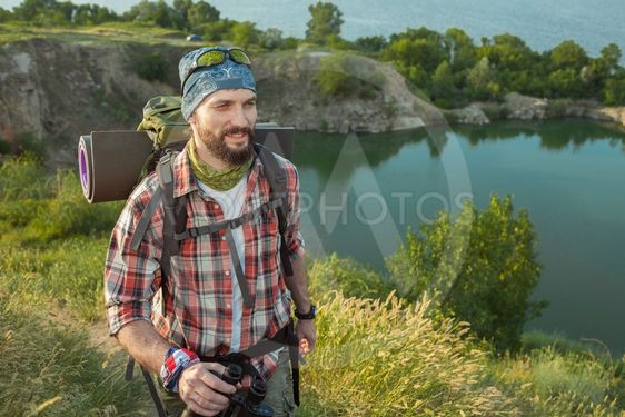 Young caucasian man with backpack walking on the top of...