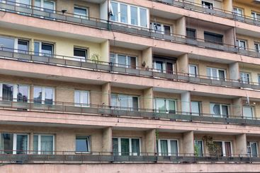 Aged apartment building with houses and balcony