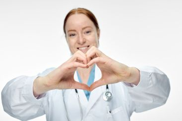 young smiling female doctor making heart sign with her...