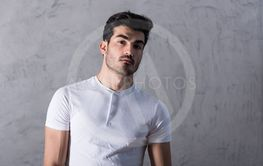 A serious young man in a white tshirt