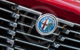 logo on red vintage alfa romeo front car parked in the...