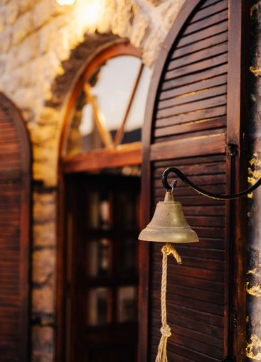 Metal bell with rope against the background of a wooden...