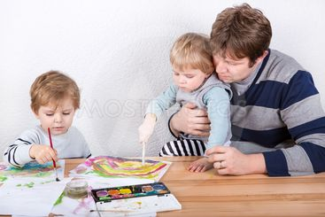 Father and two little boys siblings having fun painting