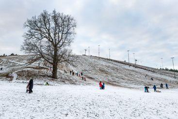 Människor i snön vid skidbacke åker pulka och skidor.
