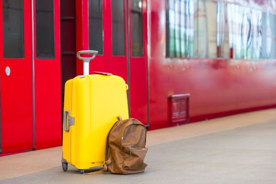 Yellow luggage with passports and brown backpack at train...