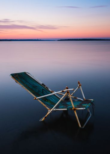 Rusty, broken chair in a shallow lake at sunset