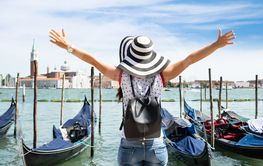 Carefree Female Tourist Standing In Front Of Gondolas