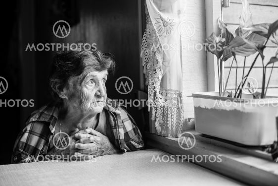 An elderly lady sits sadly near the window of his old...