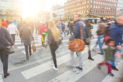Blurred crowd of people walking on zebra crossin in...
