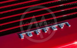 Ferrari logo on red sport car rear view parked in the...