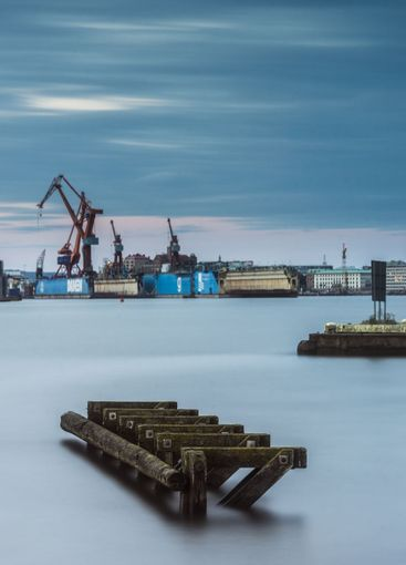 Wooden dock in dense fog with a shipyard in the background