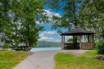 Vacker picknick och rastplats med ute grill vid vattnet.