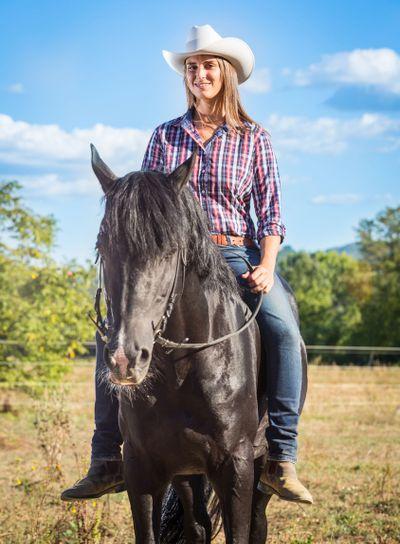 Cowgirl Riding a Black Stallion Horse