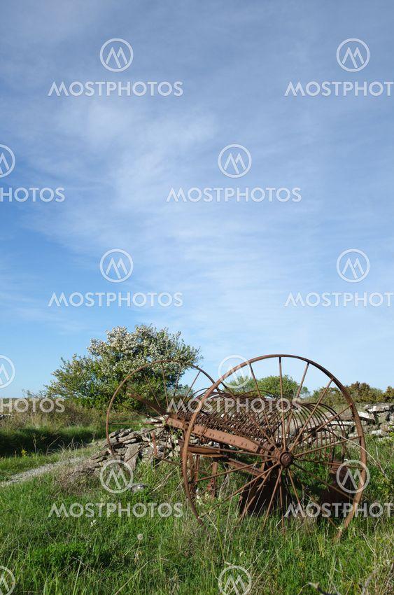 Abandoned old horse rake in a landscape at springtime