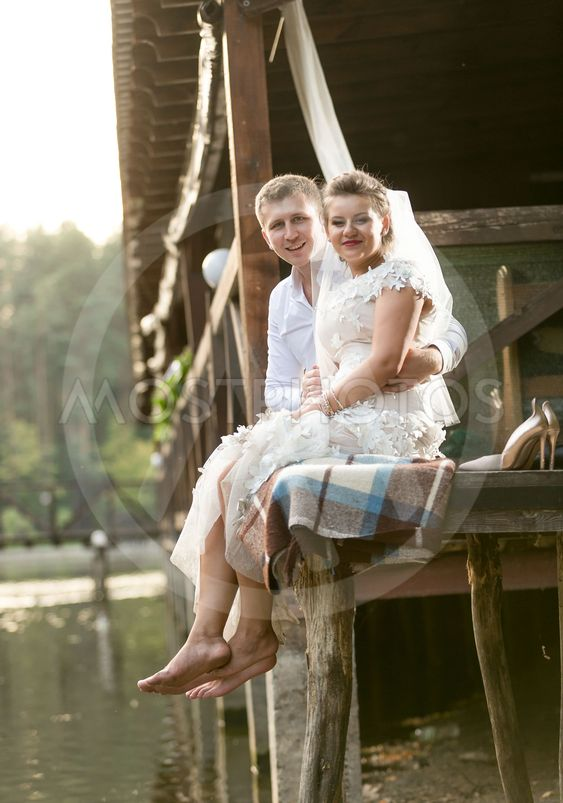 newly married couple sitting next to river at forest