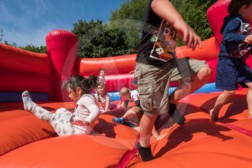 Barn leker och har roligt i en hoppborg.