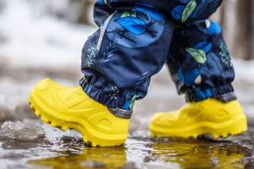small child in yellow rubber walks through puddles in...