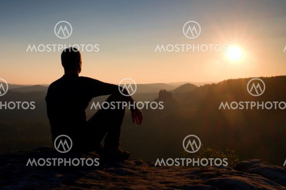 Hiker take relaxing on a rock and enjoying sunset at...
