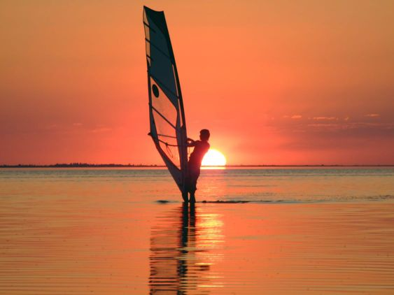 Silhouette of a windsurfer on waves of a gulf on a sunset 4