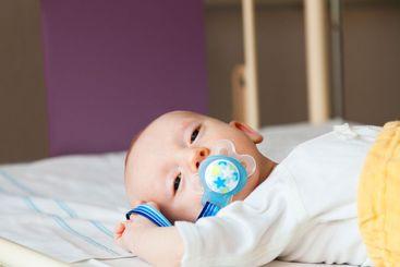 Nyfött barn med napp håller på att somna.