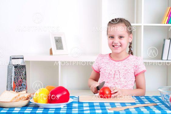 tyttö työskentelevien keittiö leikkaus vihanneksia