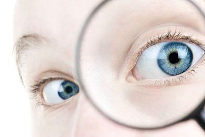 Eye looking thorough magnifying glass