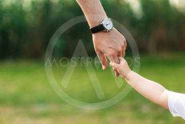 the dad holds the child by the hand. a walk in the nature