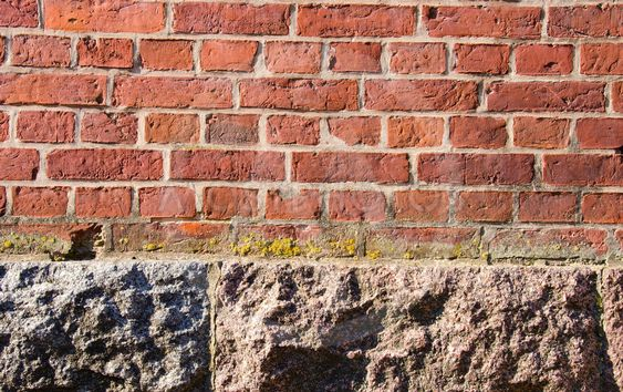 Background red brick wall stone house foundations
