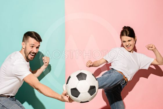 The young football fans plaing with ball on blue and pink...
