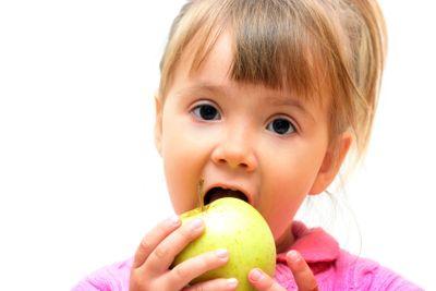 Girl eating green apple