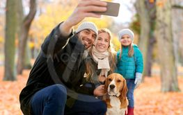 happy family with dog taking selfie in autumn park