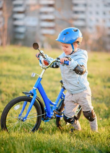 Cute child is driving a bike on a sunny day at sunset