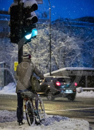 Woman with bicycle in snow at the traffic light.