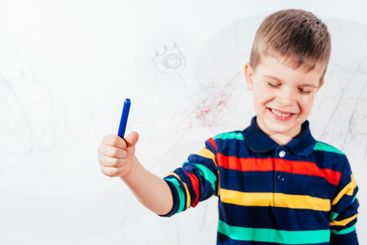 The child draws on the wall with a crayon. The boy is...