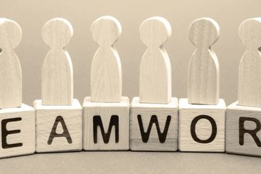 Wooden blocks with the word Teamwork and business team...