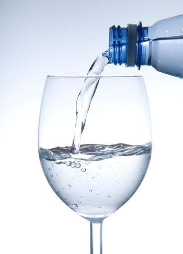 Water pouring from plastic bottle into wine glass