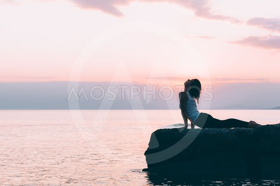 Young woman doing yoga by the sea